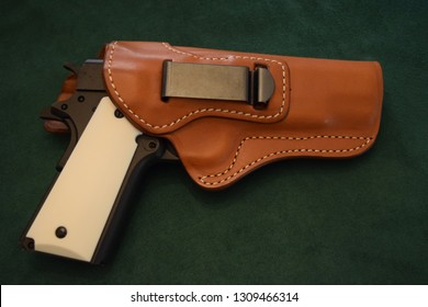 Pistol in brown leather holster on green background