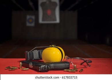 pistol, bullets, ear protection, eyeglasses at shooting range