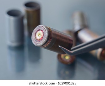 Pistol cartridge case from a crime scene. Police department forensics laboratory. Close-up, selective focus.