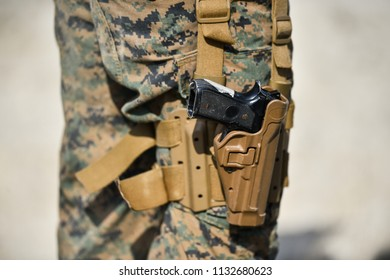 Pistol detail and military camouflage uniform on a soldier
