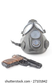 Pistol and gas mask over white background