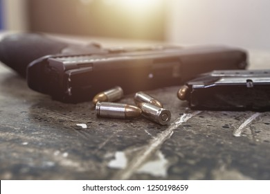 Pistol gun cartridges ammunition and knife on grunge concrete cement. Set of combat weapon concept.