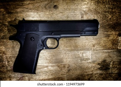 Pistol Gun isolated on wooden background. Selective focus on front gun vintage color tone. A gun is a tubular ranged weapon typically designed to pneumatically discharge projectiles.