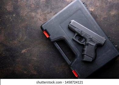 Pistol, Gun over case for gun on dark metal  table. Top view