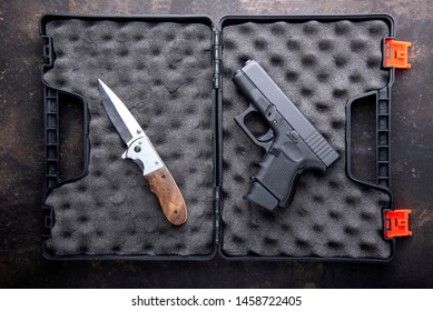 Pistol, Gun and Pocket knife in open case for gun on dark metal table. Top view