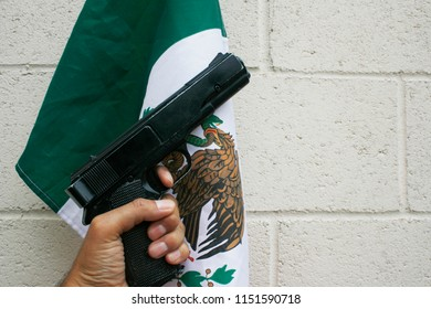A pistol is held in front of an Mexican Flag. Personal Protection. Protection of life and property. Gun Control. Guns. Civil Liberty. Crime in Mexico.