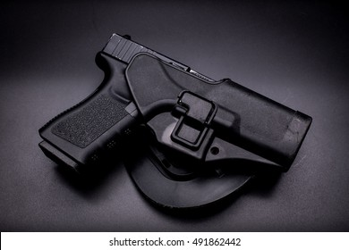 pistol in a holster in black background