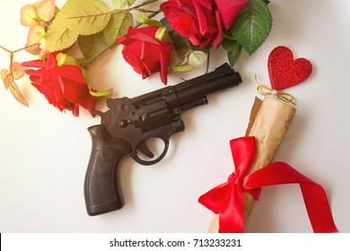 Pistol and love scroll on a wooden table