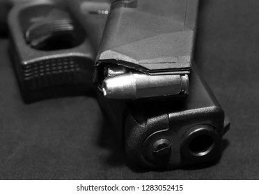 A pistol magazine loaded with 9mm bullets on top of a black 9mm semiautomatic pistol on a black background