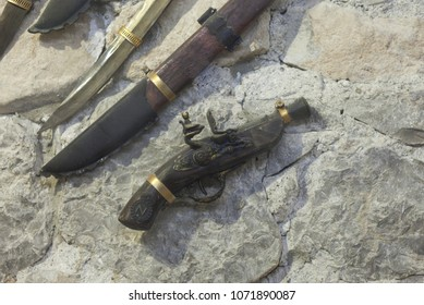 Pistol musket and swords on the wall