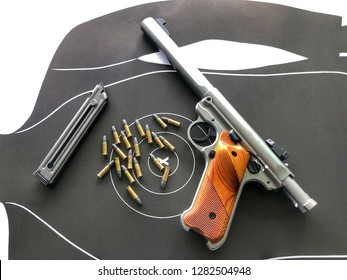 Pistol on the table or Ruger Mark IV competition pistol. Image shows the .22 caliber pistol with magazine, target and bullets at shooting range.