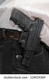 Pistol Packing/close up of holstered handgun against plain white shirt & black denim