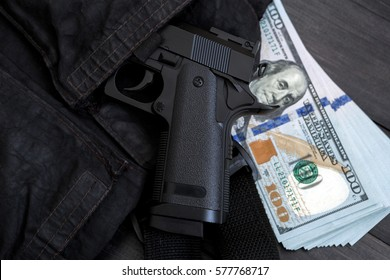 pistol peeking out of  bags  pocket and money in the background