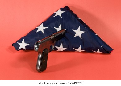 pistol pointed at a folded american flag