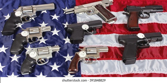 Pistols and revolver assorted firearms for sale on USA America flag at gun show