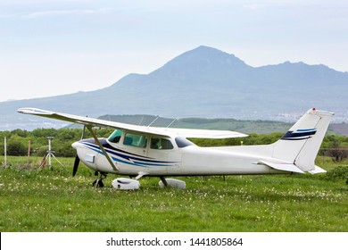 Piston aircraft. plane on the background of the mountains, the plane stands on the grass in nature
