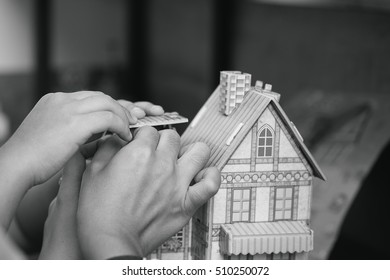 pisture of hands building paper house with monochrome effect.