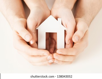 pisture of man and woman hands holding paper house