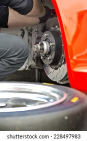 Pit crew mechanic working on the brake pads and brake disc of a red race car, with a spare tire in the foreground