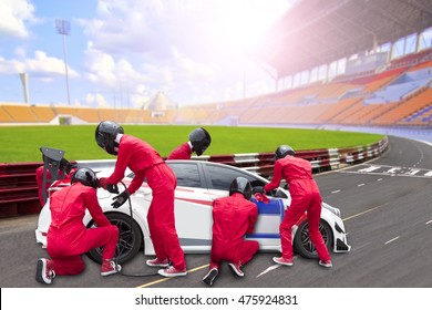 Pit stop with team maintaining technical service for a racing car during competition