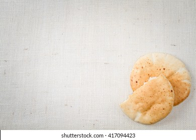 Pita or Arabic bread, soft baked flatbread on canvas background with free space for text