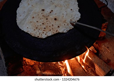 Pita bread baking on a saj or tava on fire, close-up. Traditional arabic pita bread cooking on fire