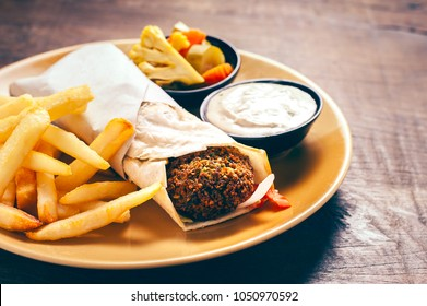Pita bread filled with falafel. Served with french fries on wooden table