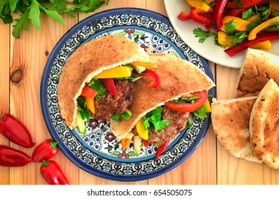 Pita bread with fried pork chop and vegetable, olive, spring picnic. Wooden background. Top view. Close-up