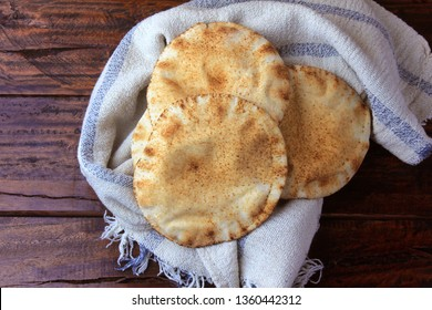 Pita bread isolated on rustic wooden table on rustic cloth. Traditional and typical food of Arabic cuisine