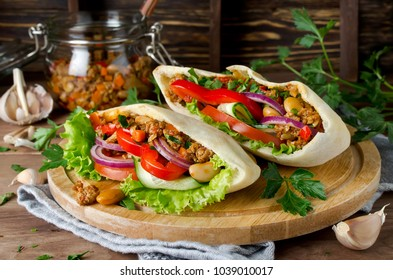 Pita bread sandwiches with meat, beans and vegetables. Served on wooden cutting board