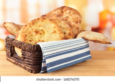 Pita breads in basket on table on bright background