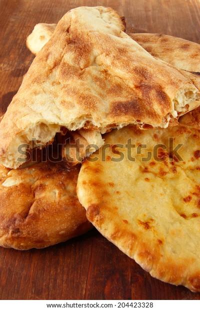 Pita breads on wooden background