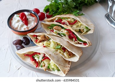 Pita filled with grilled chicken fillet, fresh salad, cucumber, sweet paprika, onion and yogurt sause on a white abstract background. Home cooking. Easy and quick snack