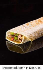 Pita meat beef and vegetables roll on black background