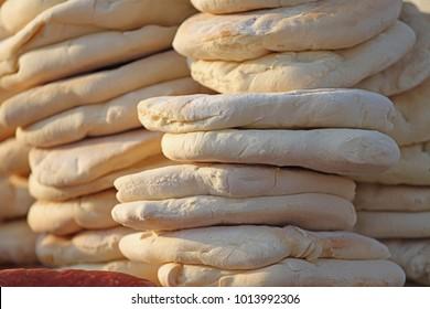 Pita. Pile of roasted pita, baked flat bread. Heap of focaccia. Lavash. Purlenka. Bread background. Flat bread background texture. Pile of roasted bread.