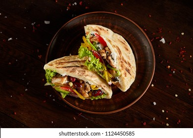 Pita stuffed with chicken, beans and letucce on clay plate over wooden background, top view, selective focus.