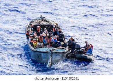 Pitcairn, Pitcairn Islands - November 22 2015: Landing at Pitcairn is tricky, Here, the island's work boat, works in tandem with the ship's zodiacs to land passengers from a visiting expedition ship.