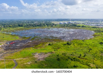 Pitch Lake, the liquid asphalt lake, the largest natural deposit of bitumen in the world.  La Brea, Trinidad island, Trinidad and Tobago. Natural asphalt mining and industrial trains of red minecarts.