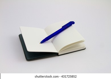 pitched black notebook with blue pen