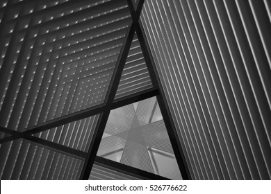 Pitched roof or ceiling. Reworked close-up photo of sloped walls. Realistic though unreal industrial interior. Abstract black and white background image on the subject of modern architecture.