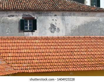 the pitched roofs of typical old painted Portuguese houses with typical fired clay tiled roofs painted walls and windows with open shutters