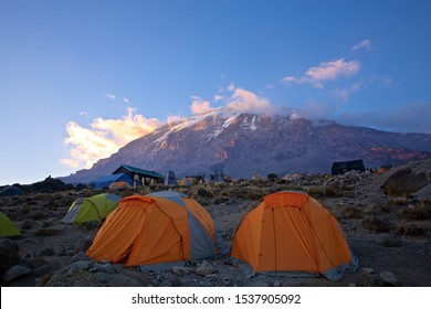 Pitched tents camping at the base of Mount Kilimanjaro just after sunrise.