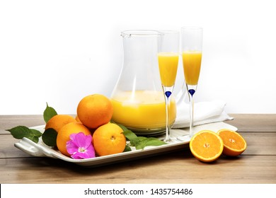 pitcher or carafe of orange cocktail  mimosa and 2 champagne flutes with oranges on the table