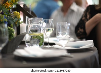 Pitcher with cold water with lemon and mint on the table in the restaurant