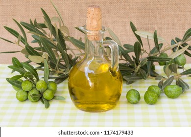 Pitcher with extra virgin olive oil and branches with fruits