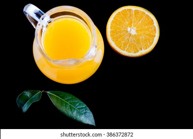pitcher of fresh orange juice on black background top view