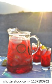 Pitcher and glasses of Hibiscus flower iced tea in Mojave Desert setting