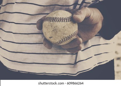 Pitcher gripping baseball for pitch in old ball game with the team.  Ball is dirty with red seam detail, held against striped shirt in background.