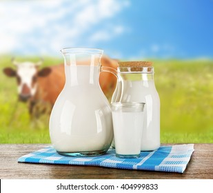Pitcher, jar and glass of milk on wooden table against cow and blue sky background