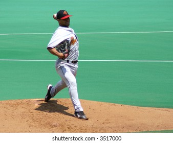 Pitcher, left-handed in the middle of a pitch, determination